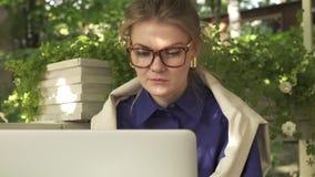 Geabsorbeerde blondevrouw in glazen die met laptop in een de zomerkoffie werken stock video