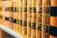 Gealterte alte alte Weinlese-Bücher auf einem Shelfs in der Bibliothek Stockfotografie
