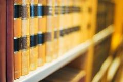 Gealterte alte alte Weinlese-Bücher auf einem Shelfs in der Bibliothek Stockbilder