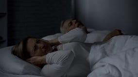 Gealterte Dame, die Hände gegen Ohren im Bett wegen des Ehemanns laut schnarcht bedrängt lizenzfreies stockfoto
