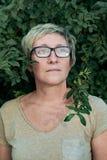 Gealterte Dame nahe dem Busch, der weg schaut Lizenzfreie Stockbilder