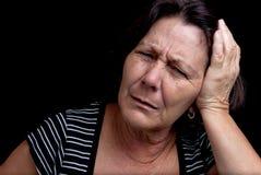Gealterte Frau, die unter starken Kopfschmerzen leidet Stockbilder