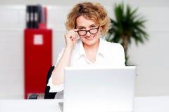 Gealterte Frauenholding-Glasfunktion auf Laptop Stockfoto