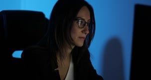 Gealterte Geschäftsfrau des Porträts arbeitet Mitte in den Gläsern am Computer im Büro in der Nacht stock video