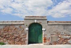 Gealterte italienische Backsteinmauer mit gewölbter Tür Lizenzfreie Stockfotos
