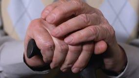 Gealterte männliche Hände auf Spazierstocknahaufnahme, Sozialpensionsreformen, Gesundheitswesen stock video