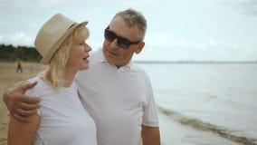 Gealterte Paare, die das Schauen in den Abstand, aktives Wochenende zusammen genießend umarmen stock video footage