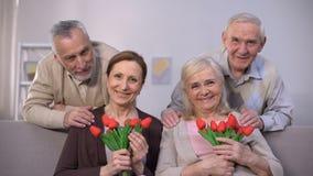 Gealterte Paare, die an der Kamera, Frauen halten Tulpen, Feier umarmen und lächeln stock video