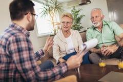 Gealterte Paare, die mit Versicherungsagenten sich beraten lizenzfreie stockfotografie
