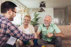 Gealterte Paare, die mit Versicherungsagenten sich beraten stockbilder