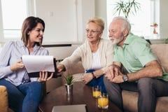 Gealterte Paare, die mit Versicherungsagenten sich beraten stockbild