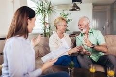 Gealterte Paare, die mit Versicherungsagenten sich beraten stockfotos