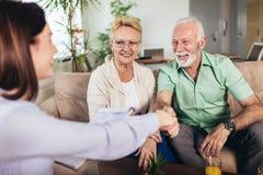 Gealterte Paare, die mit Versicherungsagenten sich beraten lizenzfreies stockfoto