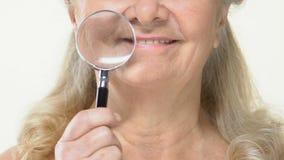 Gealterte weibliche haltene Lupe auf geknittertem altem Gesicht, Antialterskosmetik stock video