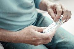 Gealterter älterer Mann, der Pillen sitzt und hält lizenzfreie stockbilder