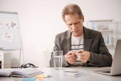 Gealterter Bürovorsteher, der unter den hohen Schmerz im Büro leidet Lizenzfreie Stockbilder