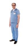 Gealterter Doktor, der mit Stethoskop um sein NEC aufwirft stockbild