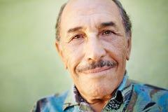 Gealterter Latinomann, der an der Kamera lächelt Stockfotografie