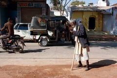 Gealterter Mann geht auf die verkehrsreiche Straße lizenzfreies stockbild