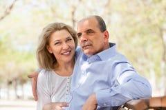 Gealterter Mann und Frau, die auf einer Bank umarmt Stockfotos