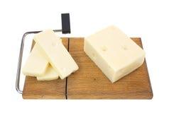 Gealterter Schweizer Käse mit Scheiben auf Ausschnittvorstand Lizenzfreie Stockfotos