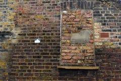 Gealtertes Gebäude mit Ziegelstein bedeckte blindes Fenster Stockbilder