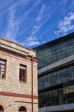 Gealtertes neoklassisches Gebäude gegen moderne Architektur, in Athen, Griechenland Stockfotografie