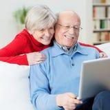 Geamuseerd hoger paar die een laptop computer met behulp van Stock Foto's