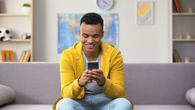 Geamuseerde Afrikaans-Amerikaanse jonge mannelijke het scrollen smartphone, die goede aanbieding ontvangen stock video