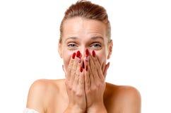 Geamuseerde jonge vrouw die haar gelach proberen te verstikken stock foto