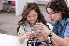 Geamuseerde kinderen die wetenschapsklasse hebben op school stock afbeeldingen