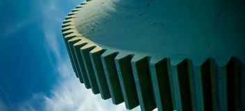 Gear. Detail of a gear wheel against the blue sky stock image