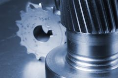 Gear-axel and cog still-life. Gears and cog against bluish aluminum stock images
