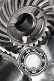 Gear and ball bearing concept. Titanium gears and ball-bearing, blue toning idea, close-up concept Stock Images