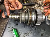 Gear of the car. Hand of the technician is holding the gear of the car removed from the engine to replace the gear Stock Photo