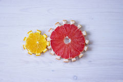 Gear drive made of citrus slices. On wooden background Royalty Free Stock Image
