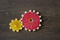 Gear drive made of citrus slices. On wooden background Stock Photography