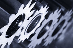 Gear-machinery in action. Gear-mechanism and its reflection in a metallic blue cast Royalty Free Stock Photos