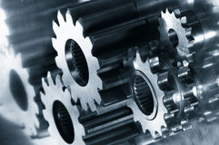 Gear-mechanism in dark blue. Gear-mechanism and its reflection in a metallic blue cast against stainless-steel Stock Images