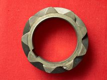 Gear wheel. Metal gear wheel on red textile background Royalty Free Stock Images