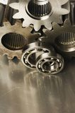Gear-wheels and ball-bearings. Two ball-bearings in front of cogs stock photos