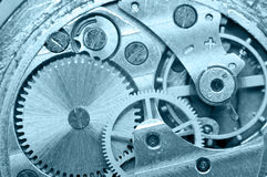 Gear wheels inside clock. Concept Teamwork. Macro Stock Photos