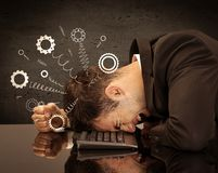 Gear wheels jumping from depressed head. Falling apart illustration concept with cranks, cog wheels springing from a fed up and tired businessman`s head resting stock image