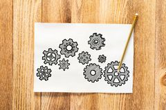 Gear wheels pencil hand drawn. Industry mechanism with cogwheels sketch on wooden surface. Artist workplace with sheet of paper and pencil lying on wooden desk stock photo