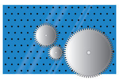 Gear wheels. Three metal gear wheels on perforated blue background Stock Photos