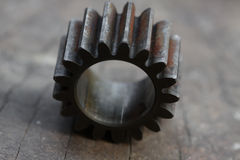 Gear on wooden background, Machine parts or spare parts, industry background, old gear or damaged gear from hard work.  Stock Images