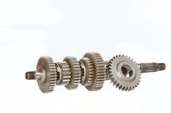 Gearbox mainshaft. A gearbox mainshaft and with a single gear cog resting against it, shot in studio over a white background stock photography