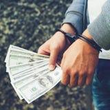 Gearresteerde gewelddadig in handcuffs die dollarbankbiljet tellen Gearresteerd F royalty-vrije stock afbeelding
