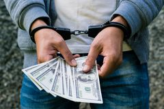 Gearresteerde gewelddadig in handcuffs die dollarbankbiljet tellen Gearresteerd F stock foto's