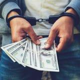 Gearresteerde gewelddadig in handcuffs die dollarbankbiljet tellen Gearresteerd F royalty-vrije stock foto's